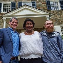 black woman and two white men smiling in front of a house