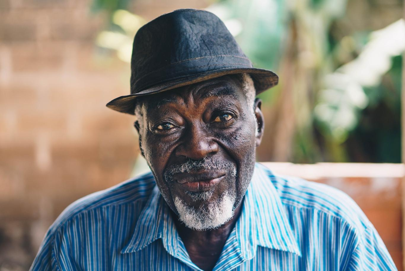 An African American elderly man wearing a hat smiles from his seat on his porch