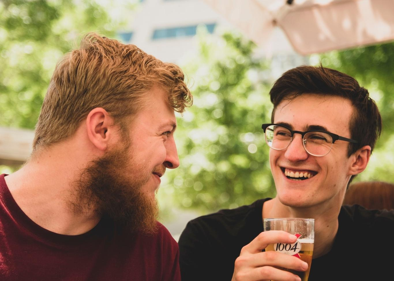 Two young men laugh while sitting outdoors on a restaurant patio