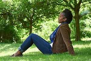 black woman sitting on the grass in the park