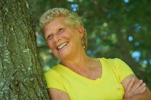 older white woman with yellow shirt smiling next to a tree