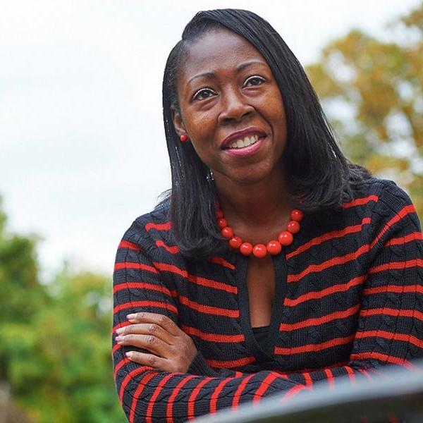 black woman in a black and red striped shirt smiling