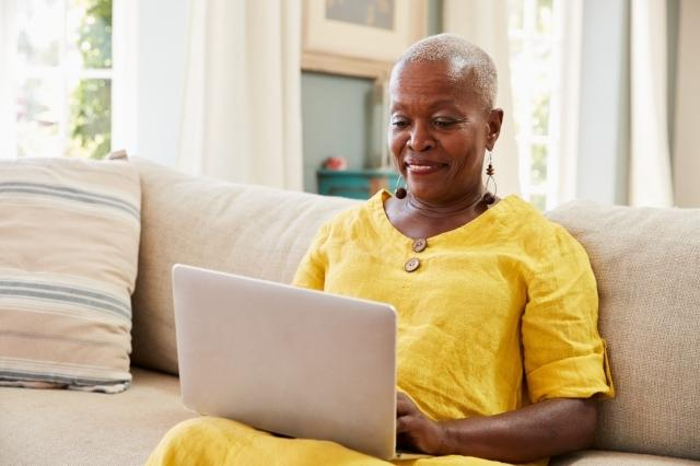 black woman in yellow typing on her computer