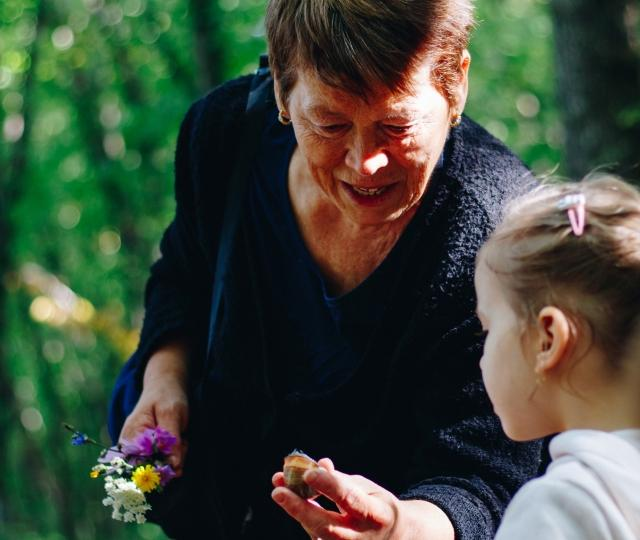 A grandmother smiles while picking wildflowers with her granddaughter