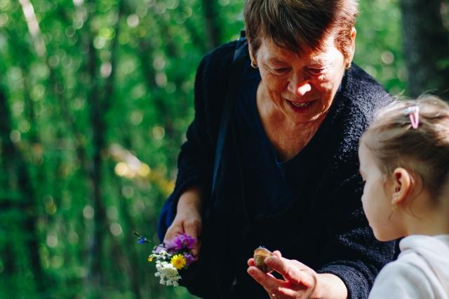 grandmother picks flowers with her granddaughter